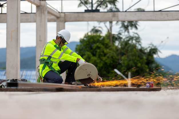 Asiatischer älterer arbeiter, der stahl auf der dachfachwerkbaustelle schneidet