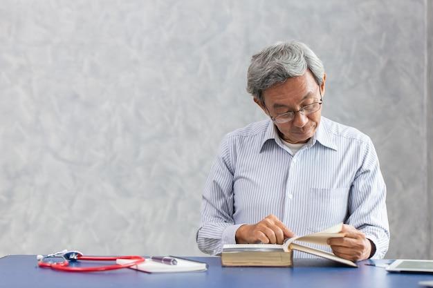 Asiatischer älterer arzt, der ein buch in der klinikklinik liest, um eine neue forschungsstudie über das koronavirus zu lernen.