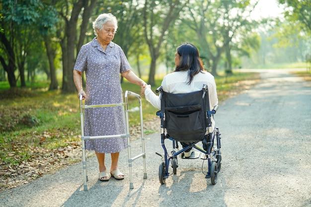 Asiatischer älterer damenweg mit wanderer und frau auf rollstuhl im park.