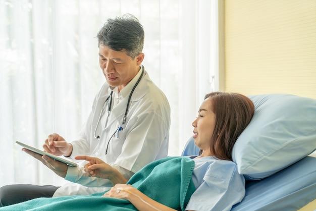 Asiatischer älterer doktor, der auf krankenhausbett sitzt und mit weiblichem patienten sich bespricht
