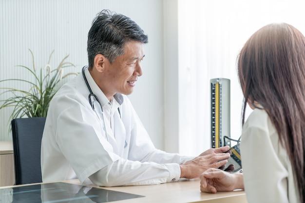 Asiatischer älterer doktor und patient besprechen sich