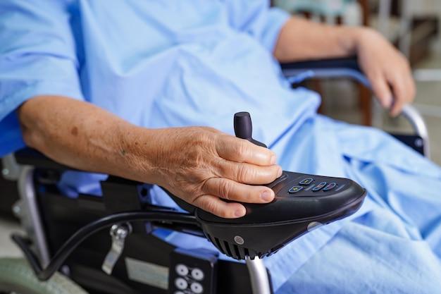 Asiatischer älterer frauenpatient auf elektrischem rollstuhl im krankenhaus.
