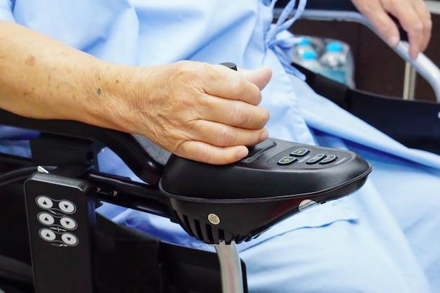 Asiatischer älterer frauenpatient auf elektrischem rollstuhl.