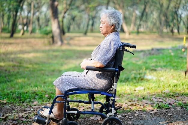 Asiatischer älterer frauenpatient auf rollstuhl im park.