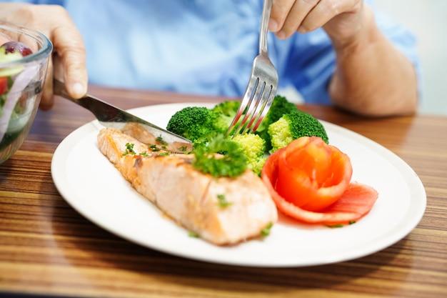 Asiatischer älterer frauenpatient der alten dame, der gesundes lebensmittel des frühstücks im krankenhaus isst.