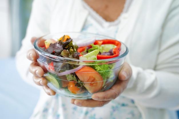 Asiatischer älterer frauenpatient der alten dame, der gesundes lebensmittel des salatgemüsefrühstücks im krankenhaus isst.
