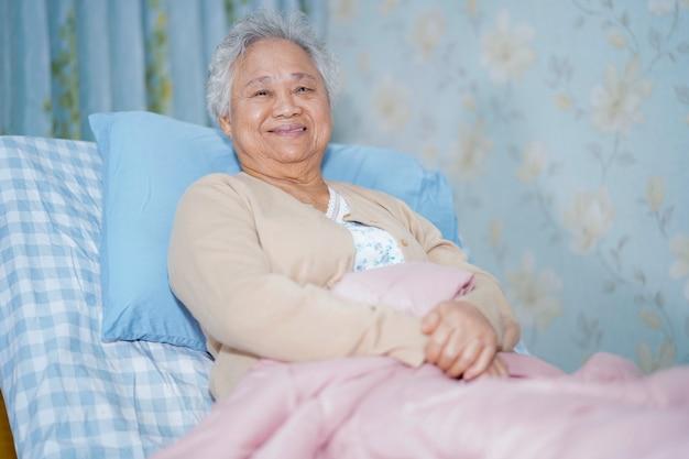 Asiatischer älterer frauenpatient, der auf bett im krankenhaus sitzt