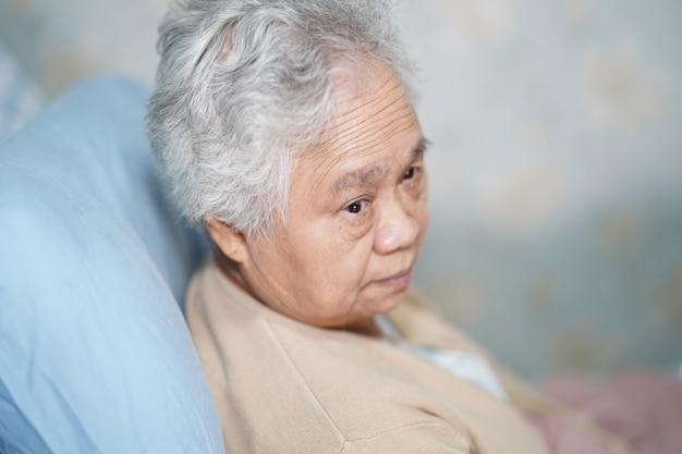 Asiatischer älterer frauenpatient, der auf bett im krankenhaus sitzt.