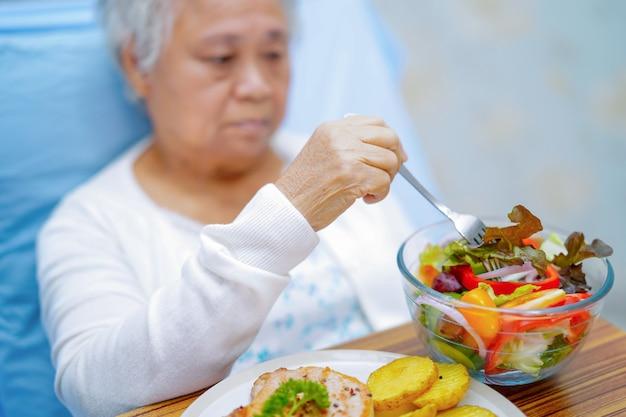 Asiatischer älterer frauenpatient, der frühstück auf bett im krankenhaus isst.