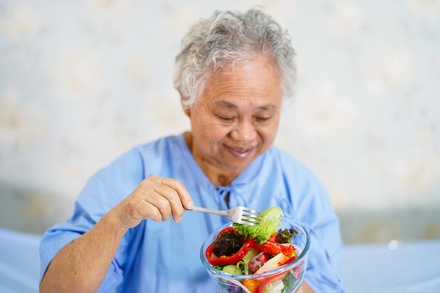 Asiatischer älterer frauenpatient, der gesundes lebensmittel des frühstücks isst.