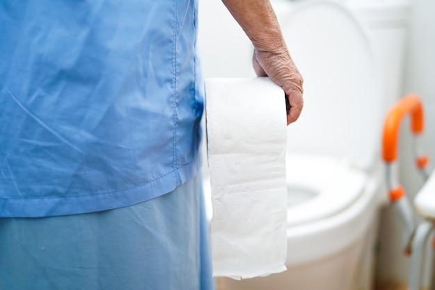 Asiatischer älterer frauenpatient in der toilette mit gewebe in krankenpflegekrankenstation
