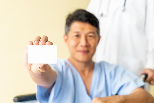 Asiatischer älterer geduldiger rollstuhl, der mit kreditkarte lächelt