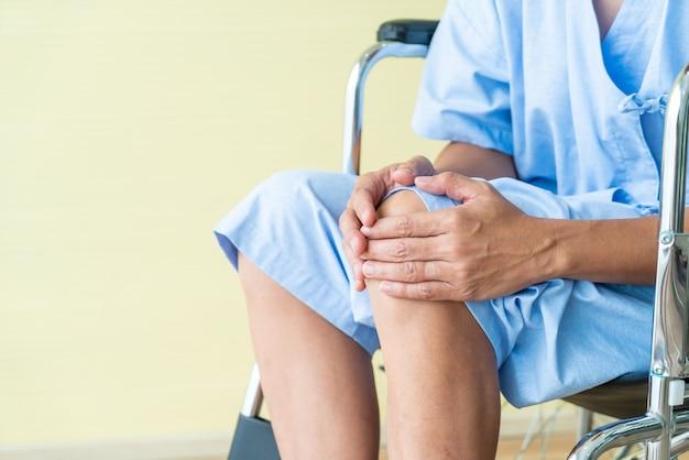 Asiatischer älterer geduldiger rollstuhl mit den knieschmerz