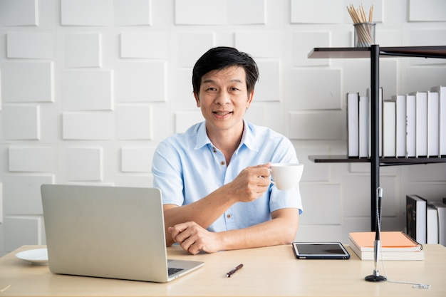Asiatischer älterer geschäftsmann 'am morgen im büro