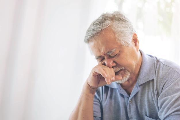 Asiatischer älterer mann, alter mann im ruhestand aufwachen mit allergien, verstopfte nase aufgrund des klimawandels, ältere patienten im bett zu hause - medizin- und gesundheitskonzept