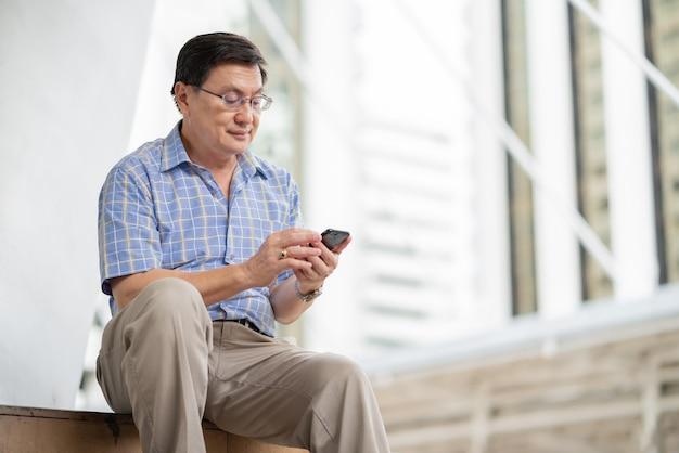 Asiatischer älterer mann, der bild auf smartphone schaut, während draußen draußen in der stadt entspannen