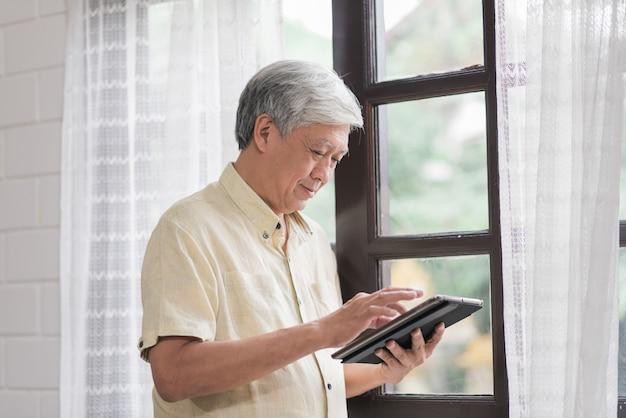 Asiatischer älterer mann, der die tablette zu hause überprüfendes social media nahe fenster im wohnzimmer verwendet. lebensstil ältere männer zu hause konzept.