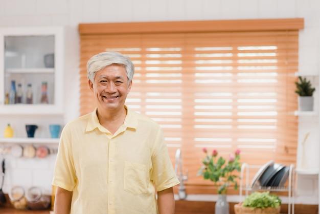 Asiatischer älterer mann, der glücklich lächelt und zur kamera schaut, während sich in der küche zu hause entspannen. lebensstil ältere männer zu hause konzept.