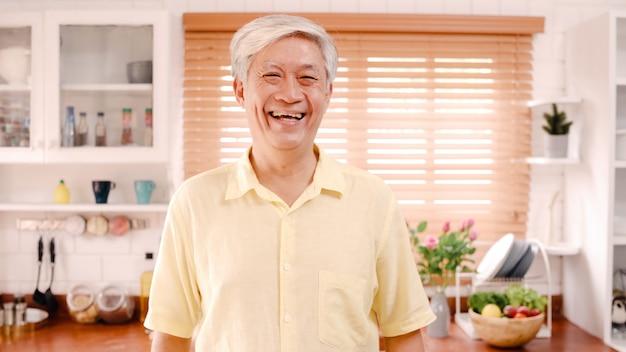 Asiatischer älterer mann, der glücklich lächelt und zur kamera schaut, während sich in der küche zu hause entspannen.