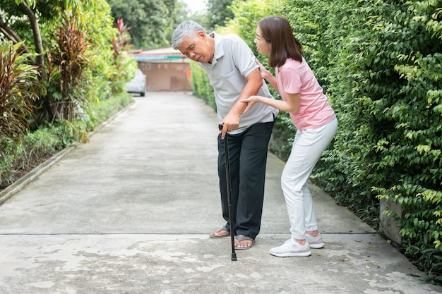 Asiatischer älterer mann, der im hinterhof ging und schmerzhafte steifheit der gelenke und der tochter kam, um unterstützung zu helfen.