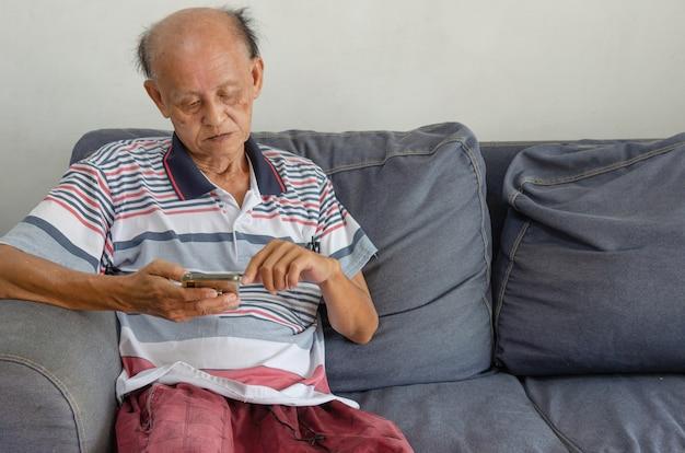 Asiatischer älterer mann, der sein telefon auf dem blauen sofa im haus betrachtet