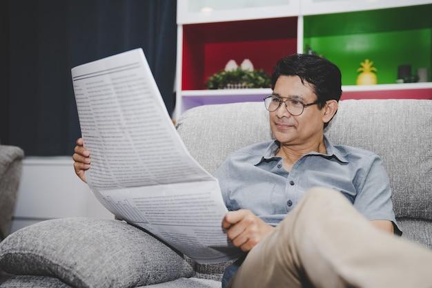 Asiatischer älterer mann, der sich zu hause business news-zeitung auf sofa im wohnzimmer entspannt und liest