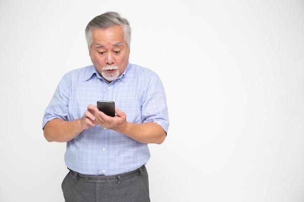 Asiatischer älterer mann, der smartphone verwendet und gute nachrichten von der nachricht auf der mobilen chat-anwendung über weiße wand, wow und überraschtes konzept erhält