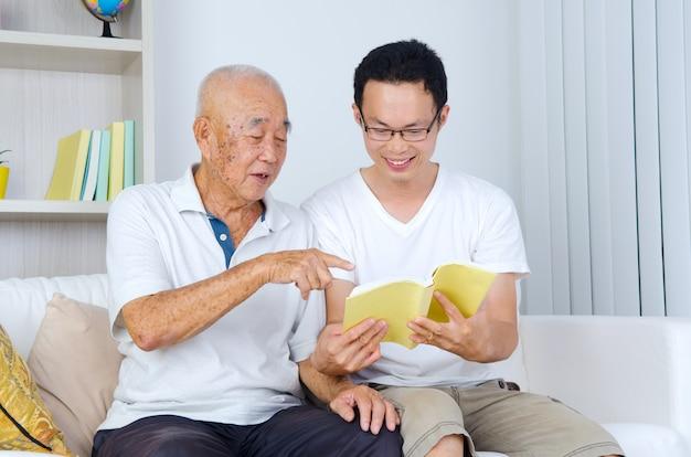 Asiatischer älterer mann, der zu hause ein buch mit seinem sohn liest