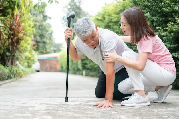 Asiatischer älterer mann, der zu hause im hinterhof fällt, verursacht durch muskelschwäche der myasthenie