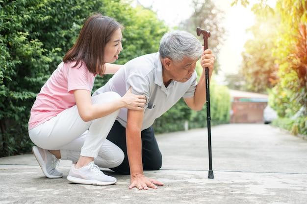Asiatischer älterer mann, der zu hause im hinterhof fällt, verursacht durch myasthenie (muskelschwäche)