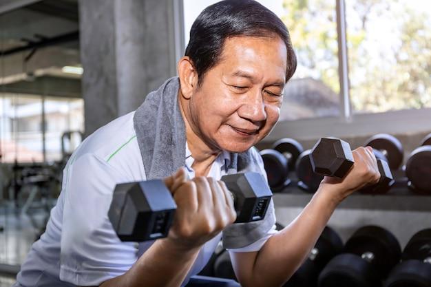 Asiatischer älterer mann im sportkleidungstraining mit dummkopf an der turnhalle.