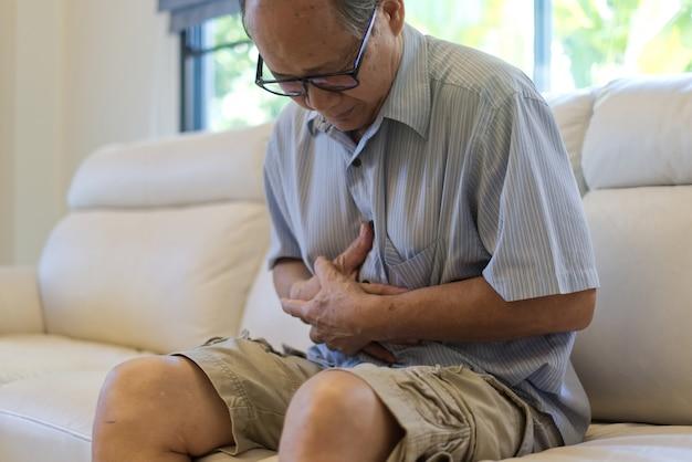 Asiatischer älterer mann leidet unter magenschmerzen.