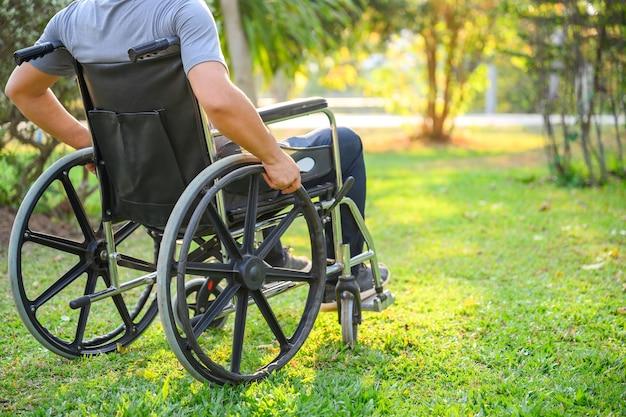 Asiatischer älterer mann menschen mit behinderungen können nicht laufen. sitzen im rollstuhl oder im rollstuhl im park, leider im rollstuhl sitzend