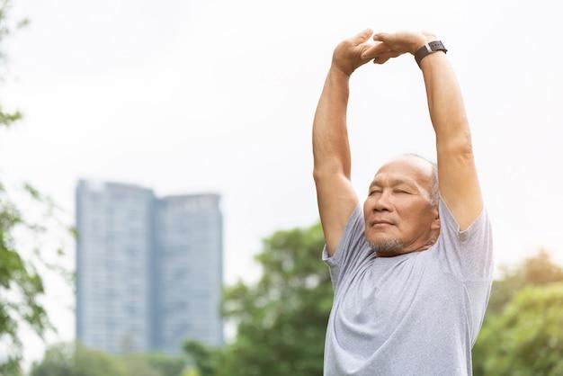 Asiatischer älterer mann streckte seine arme in der luft vor dem training aus.