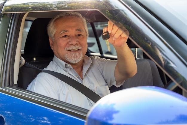 Asiatischer älterer mannfahrer, der lächelt und neue autoschlüssel zeigt und im auto sitzt