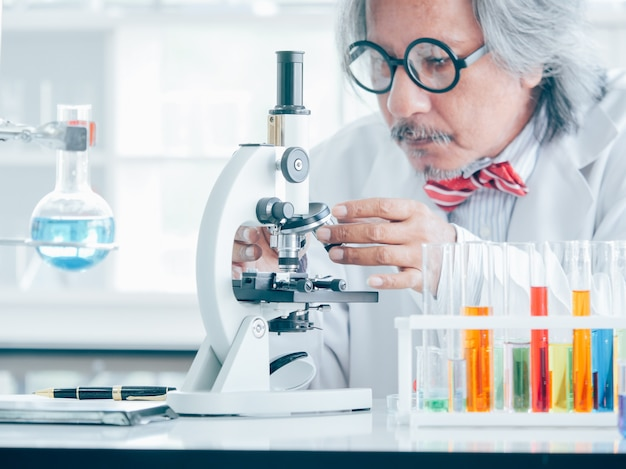 Asiatischer älterer medizinischer forschungswissenschaftler, der im schoss arbeitet