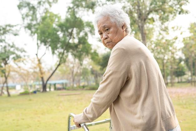 Asiatischer älterer oder älterer alter frauenpatient spaziergang mit wanderer im park mit kopienraum, gesundes starkes medizinisches konzept