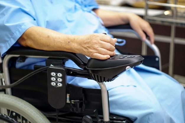 Asiatischer älterer oder älterer frauenpatient alter dame auf elektrischem rollstuhl an der krankenpflegekrankenhaus