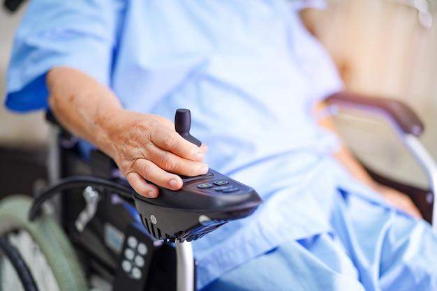 Asiatischer älterer oder älterer frauenpatient alter dame auf elektrischem rollstuhl mit fernbedienung an der krankenstation.