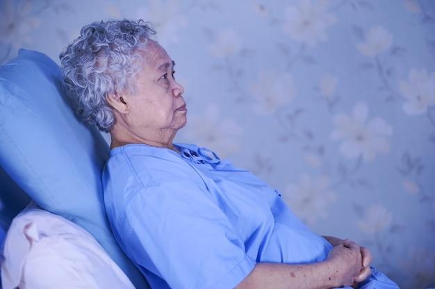 Asiatischer älterer oder älterer frauenpatient alter dame, der auf bett in krankenpflegekrankenstation sitzt.