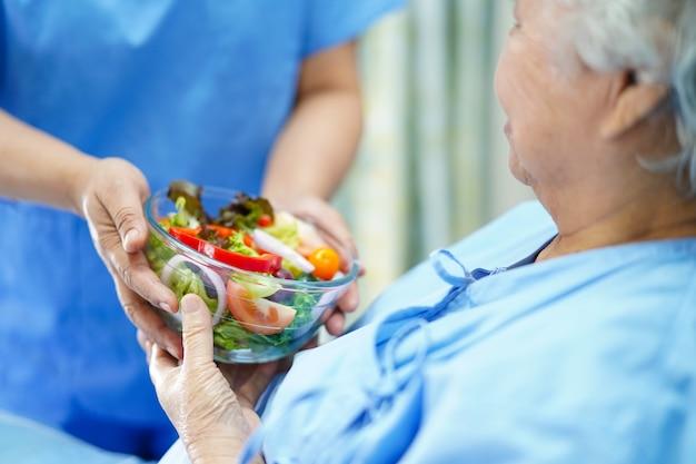 Asiatischer älterer oder älterer frauenpatient alter dame, der gesundes lebensmittel im krankenhaus hält.