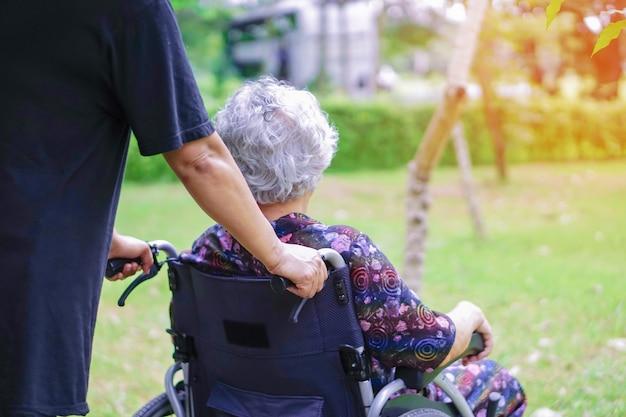 Asiatischer älterer oder älterer frauenpatient der alten dame auf rollstuhl im park.