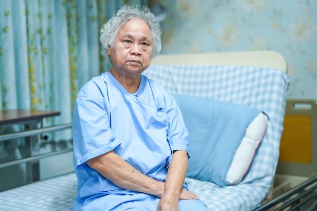 Asiatischer älterer oder älterer frauenpatient der alten dame, der auf bett in krankenpflegekrankenhaus sitzt.