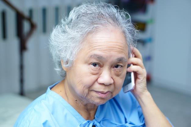 Asiatischer älterer oder älterer frauenpatient der alten dame, der durch handy spricht.