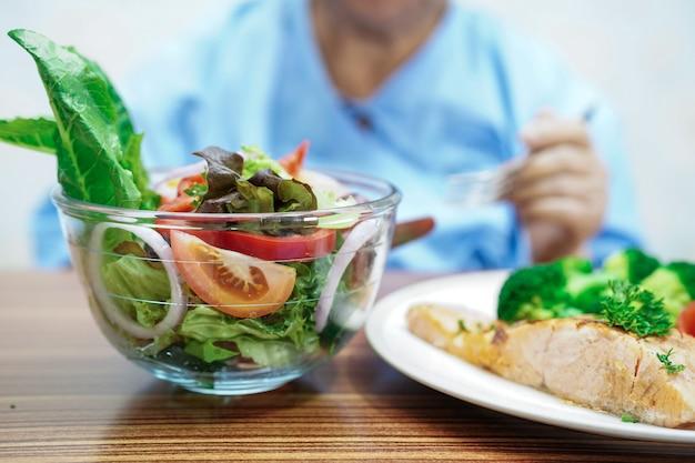 Asiatischer älterer oder älterer frauenpatient der alten dame, der gesundes lebensmittel des gemüsefrühstücks des lachssalats mit hoffnung isst