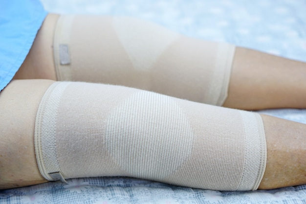 Asiatischer älterer oder älterer frauenpatient der alten dame mit knieschutzschmerzgelenk.