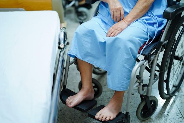 Asiatischer älterer oder älterer fraupatient, der auf rollstuhl im krankenhaus sitzt