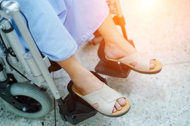 Asiatischer älterer oder älterer fraupfleger der alten dame auf elektrischem rollstuhl am pflegeheim