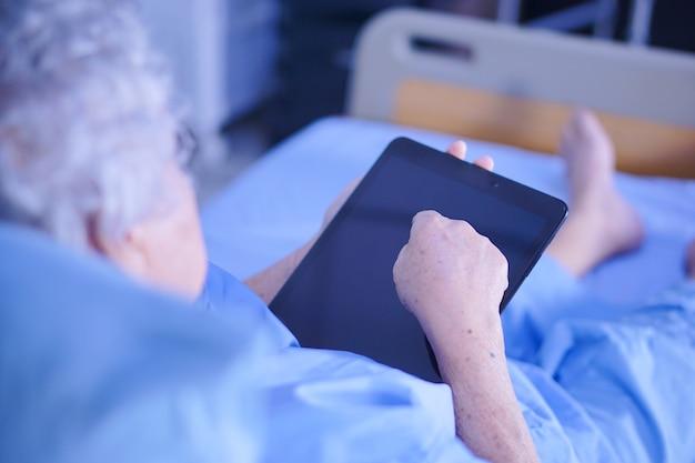 Asiatischer älterer oder älterer fraupfleger der alten dame, der in ihrer handdigitalen tablette hält.