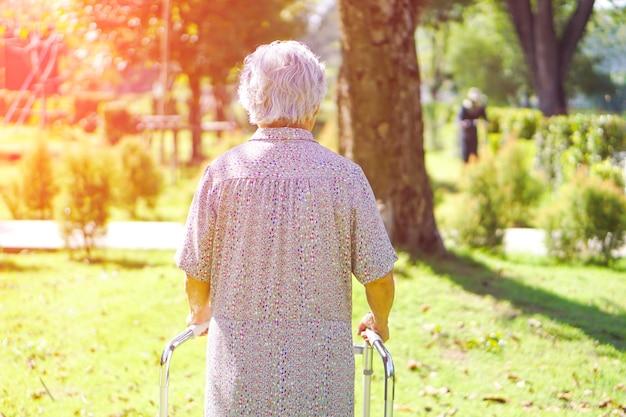 Asiatischer älterer oder älterer gebrauchender wanderer der alten dame mit starker gesundheit beim gehen am park.